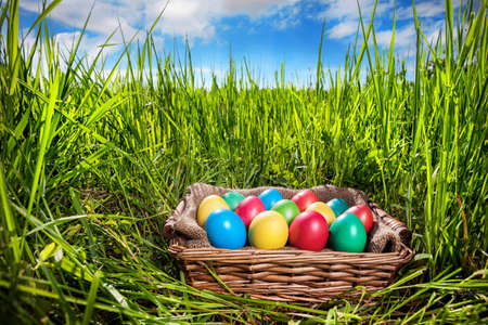 Easter colorful eggs in the basket on the green grass at blue sky photo