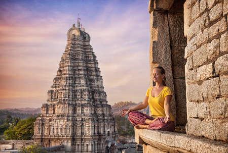 Vrouw doet meditatie buurt Virupaksha tempel in Hampi, Karnataka, India