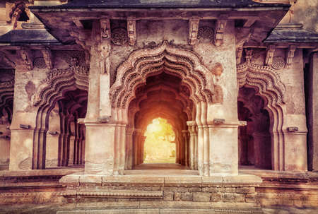 Old ruined arches in Lotus Mahal at sunset in Hampi, Karnataka, India photo