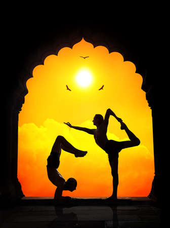 ashram: Two men in silhouette doing yoga difficult poses in old temple at orange sunset sky background Stock Photo