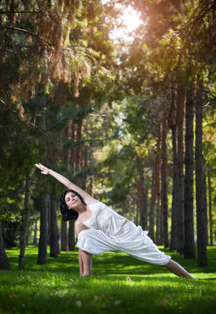 parsvakonasana: Woman in white costume doing yoga on the green grass in the park around pine trees
