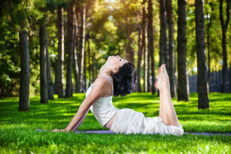 Woman in white costume doing yoga on the green grass in the park around pine trees