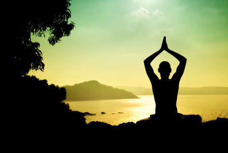 Man silhouette in Yoga meditation pose near the ocean in Gokarna, Karnataka, India Stock Photo