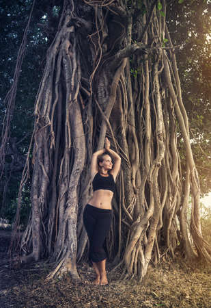 Woman in black costume posing near big banyan tree in Goa, India photo