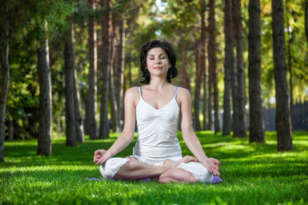 dhyana: Woman in meditation pose on the green grass in the park around pine trees