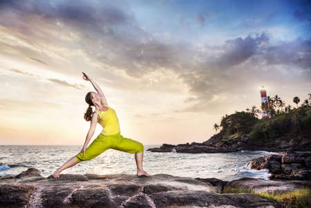 yoga rocks: Woman doing yoga on the stone nearby ocean at lighthouse background in Kovalam, Kerala, India Stock Photo