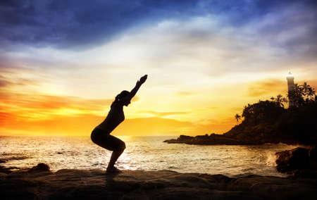 Woman doing Yoga Utkatasana pose in silhouette on the stones near lighthouse at sunset sky in Kovalam, Kerala, India