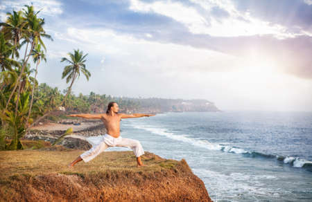 varkala: Man doing yoga in white trousers on the cliff near the ocean in Kerala, India Stock Photo