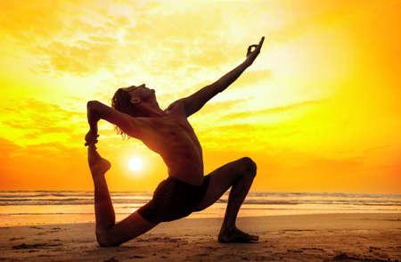 Man doing Yoga on the beach near the ocean in India photo