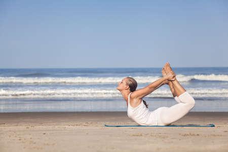 Yoga dhanurasana bow pose by woman in white costume on the beach near the ocean in Goa, India Zdjęcie Seryjne - 26863043