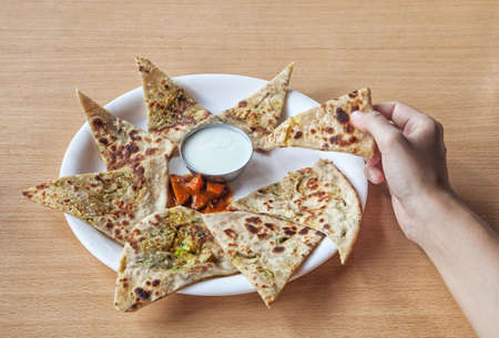 Woman holding Indian traditional aloo paratha in restaurant     photo