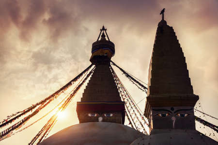 bodnath: Two Buddhist stupas silhouettes with glowing eyes at sunset in Bodhnath, Kathmandu valley, Nepal