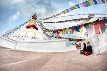 BODNATH, KATHMANDU, NEPAL - APRIL 6, 2014  Man and woman doing meditation near Bodnath stupa, center of Buddhism pilgrimage