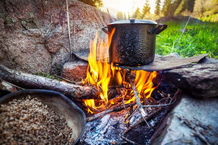 Tourist breakfast cooking on bonfire in the mountain forest, Almaty, Kazakhstan photo