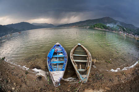 tal: Wooden boats on the shore of Fewa Tal at storm overcast sky in Pokhara, Nepal Stock Photo