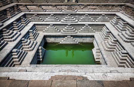 Stepped tank with green water in Pushkarani, Hampi, Karnataka, India photo