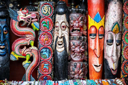 Souvenir masks, Chinese dragon and om symbols on the wall in the shop of Pokhara, Nepal    photo