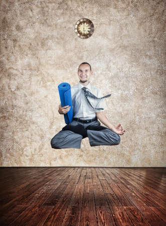 levitacion: Empresario celebraci�n estera de yoga y hacer levitaci�n en posici�n de loto en la sala de yoga con el reloj en la pared