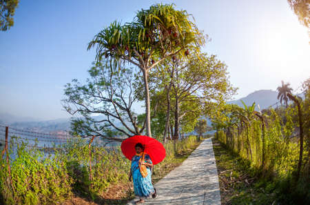 tal: POKHARA, NEPAL - APRIL 21, 2014  Nepali woman with red umbrella walking down the road near Fewa Tal in the morning Editorial