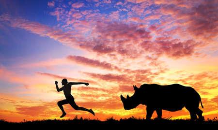 Hombre huyendo de rinoceronte al atardecer en la sabana Foto de archivo