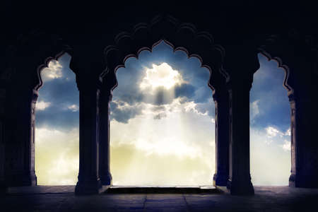 Indian arch silhouette in old temple at dramatic sunset sky with light hole in the clouds Zdjęcie Seryjne