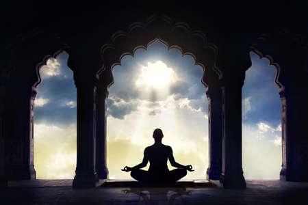 moine: Méditer dans le vieux temple avec des arcs décoratifs au dramatique ciel coucher de soleil avec le trou de la lumière dans les nuages Banque d'images