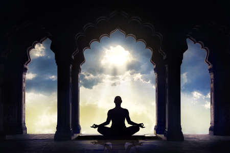 Meditating in old temple with decorative arches at dramatic sunset sky with light hole in the clouds