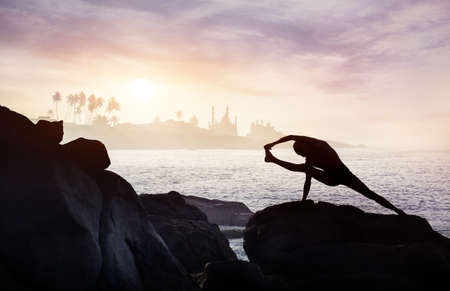Man silhouette doing Yoga on the rocks near the ocean at mosque background photo