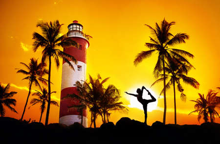 Man doing Yoga dancer pose in silhouette near lighthouse at sunset sky in Kovalam, Kerala, India photo