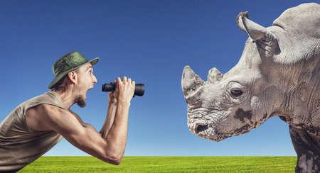encounter: Man with binocular screaming at rhino in grassland at blue sky