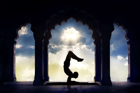 pose: Man silhouette doing yoga advance scorpion pose in old temple at sunset sky background Stock Photo