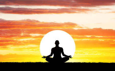 Man silhouette in Yoga meditation pose at big sun background