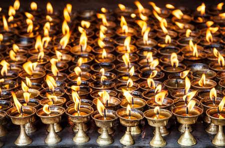 Butter lamps with flames near Bodhnath stupa in Kathmandu valley, Nepal photo