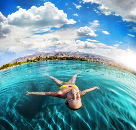 issyk kul: Woman laying like a star in Issyk Kul lake at mountains background in Kyrgyzstan, central Asia Stock Photo