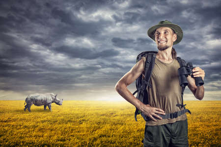 Man with binocular and rhino behind in grassland at sunset overcast sky photo