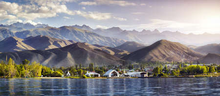 issyk kul: View to Ruh Ordo cultural complex near Issyk Kul lake at mountains background in Cholpon Ata, Kyrgyzstan Stock Photo