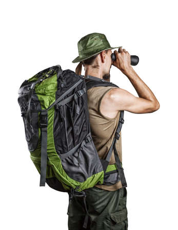 Man with backpack looking through the binocular from the back isolated on white background photo