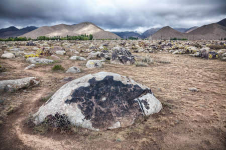 issyk kul: Ancient petroglyph with hunter and animals on the stone in Kyrgyzstan at overcast mountain background  Stock Photo