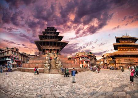 kathmandu: BHAKTAPUR, KATHMANDU VALLEY, NEPAL - APRIL 8, 2014: People walking near Nepalese temples in shape of pagoda at Durbar Square