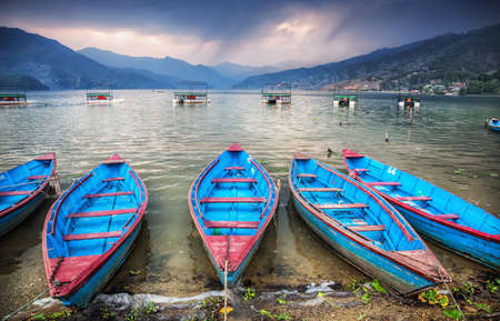 tal: Wooden blue boats on the shore of Fewa Tal at storm overcast sky in Pokhara, Nepal