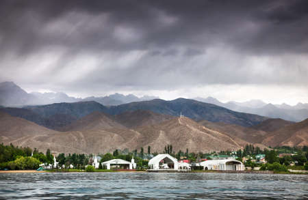 View to Ruh Ordo cultural complex near Issyk Kul lake at mountains and overcast sky in Cholpon Ata, Kyrgyzstan