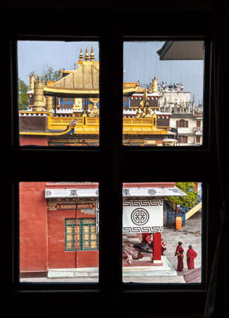 bodnath: BODNATH, KATHMANDU, NEPAL - APRIL 6, 2014: Monks in red robes standing in the yard of Buddhist monastery Sakya Tharig gompa