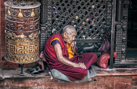 bodnath: BODNATH, KATHMANDU, NEPAL - APRIL 7, 2014: Old woman in red Buddhist robe sitting near small temple with prayer wheel at Bodnath stupa