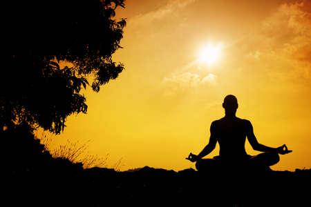 hombres haciendo ejercicio: Silueta del hombre en la meditación de la yoga cerca del árbol al atardecer en Gokarna, Karnataka, India