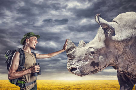 Man with binocular touching horn of rhino in grassland at sunset overcast sky photo