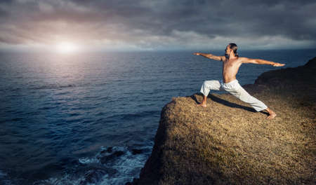 warrior pose: Man in white trousers doing Yoga warrior pose on the cliff near the ocean in Kerala, India