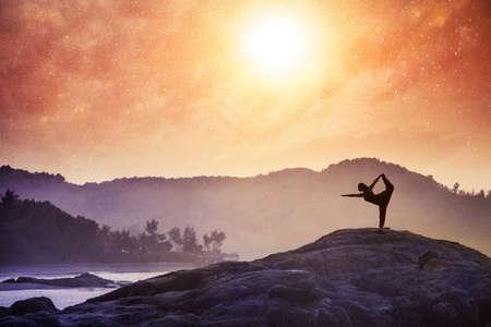 Vrouw doet yoga natarajasanadanser pose op de rotsen bij zonsondergang in Om Beach, Gokarna, India Stockfoto