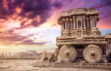 Stone chariot in courtyard of Vittala Temple at sunset purple sky in Hampi, Karnataka, India