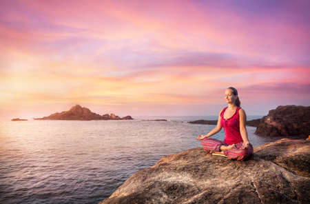 Vrouw doet meditatie in het rood kostuum op de steen in de buurt van de oceaan in Gokarna, Karnataka, India Stockfoto