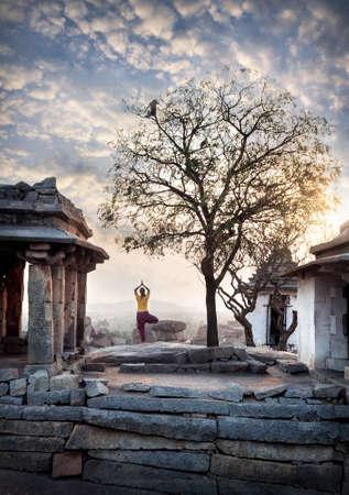 ancient yoga: Woman doing yoga near ancient ruins on Hemakuta hill in Hampi, Karnataka, India Stock Photo
